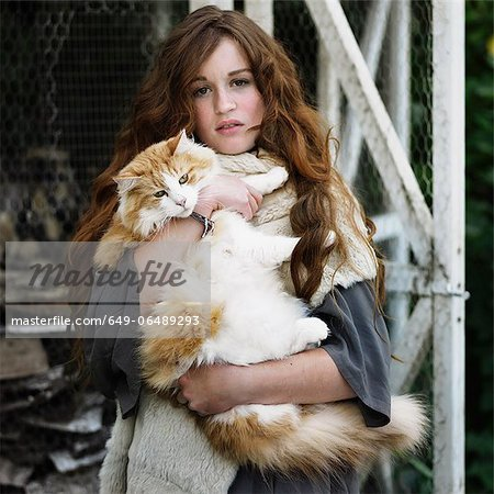 Woman holding large cat outdoors Stock Photo - Premium Royalty-Free, Image code: 649-06489293