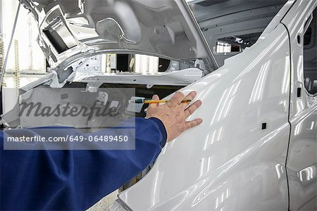 Worker inspecting car in factory Stock Photo - Premium Royalty-Free, Image code: 649-06489450
