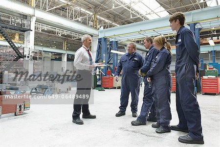 Workers and businessman in factory Stock Photo - Premium Royalty-Free, Image code: 649-06489489