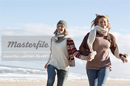 Smiling women running on beach Stock Photo - Premium Royalty-Free, Image code: 649-06489713
