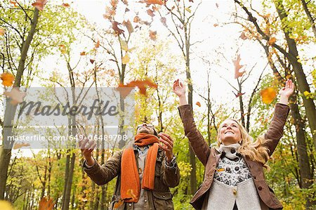 Smiling couple playing in autumn leaves Stock Photo - Premium Royalty-Free, Image code: 649-06489798