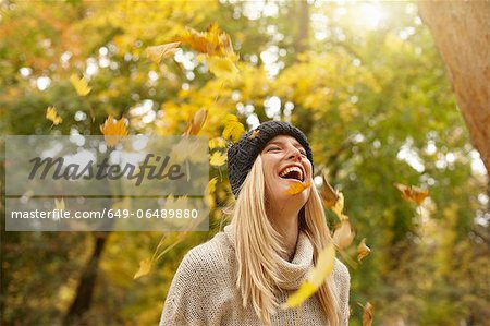 Woman playing in autumn leaves outdoors Stock Photo - Premium Royalty-Free, Image code: 649-06489880