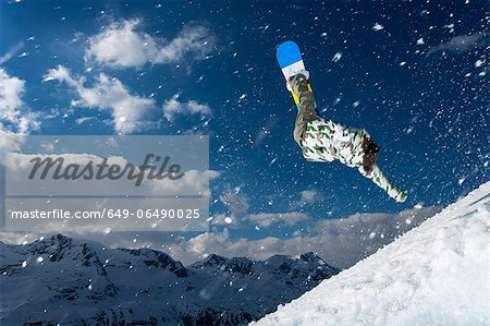 Snowboarder jumping on snowy slope Stock Photo - Premium Royalty-Free, Image code: 649-06490025