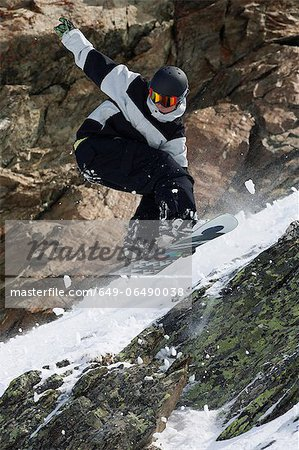 Snowboarder jumping on rocky slope Stock Photo - Premium Royalty-Free, Image code: 649-06490038