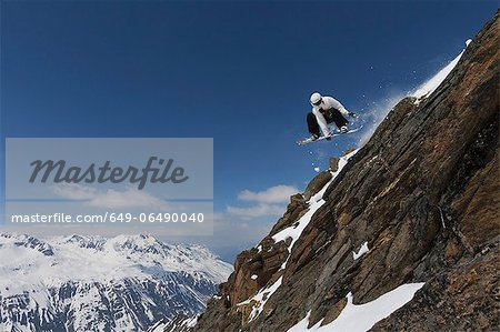 Snowboarder jumping on rocky slope Stock Photo - Premium Royalty-Free, Image code: 649-06490040