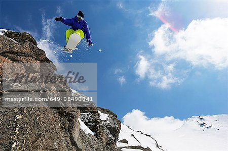 Snowboarder jumping on rocky slope Stock Photo - Premium Royalty-Free, Image code: 649-06490041