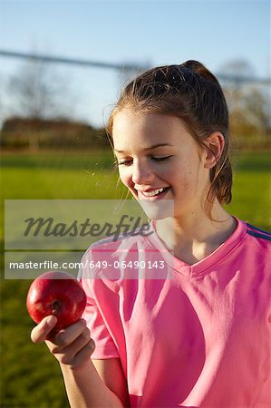 Girl eating apple in field Stock Photo - Premium Royalty-Free, Image code: 649-06490143