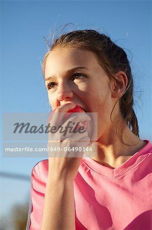 Girl eating apple outdoors Stock Photo - Premium Royalty-Free, Image code: 649-06490144