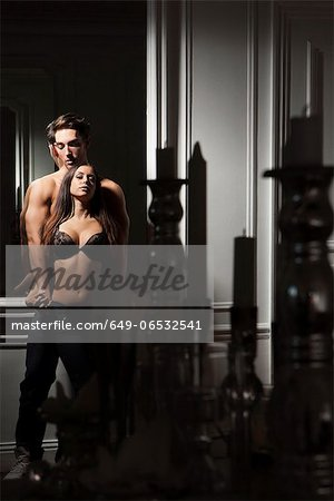 Couple hugging in dark room Stock Photo - Premium Royalty-Free, Image code: 649-06532541