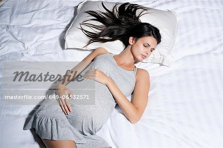 Pregnant woman sleeping in bed Stock Photo - Premium Royalty-Free, Image code: 649-06532571