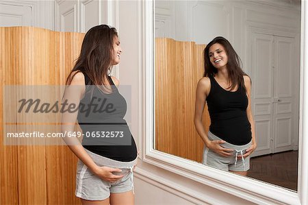 Pregnant woman admiring herself Stock Photo - Premium Royalty-Free, Image code: 649-06532573