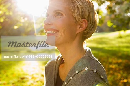 Woman smiling in park Stock Photo - Premium Royalty-Free, Image code: 649-06532681