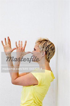 Smiling woman making face with hands Stock Photo - Premium Royalty-Free, Image code: 649-06532718