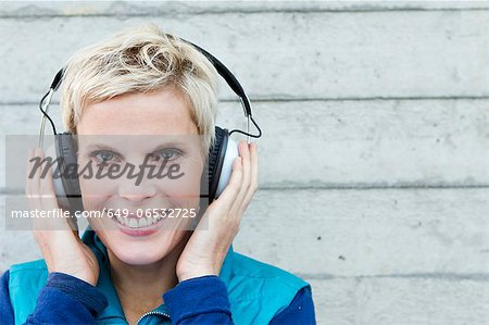 Smiling woman listening to headphones Stock Photo - Premium Royalty-Free, Image code: 649-06532725