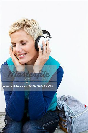 Smiling woman listening to headphones Stock Photo - Premium Royalty-Free, Image code: 649-06532726