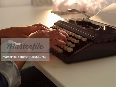 Close up of woman using typewriter Stock Photo - Premium Royalty-Free, Image code: 649-06532751
