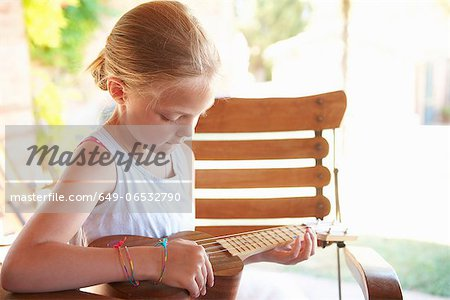 Girl strumming ukulele outdoors Stock Photo - Premium Royalty-Free, Image code: 649-06532790