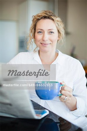 Woman drinking coffee and reading paper Stock Photo - Premium Royalty-Free, Image code: 649-06532813