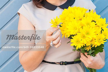 Woman holding bouquet of yellow flowers Stock Photo - Premium Royalty-Free, Image code: 649-06533048