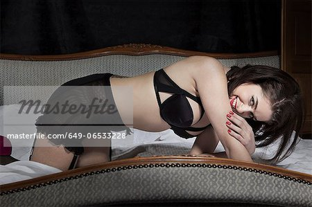 Woman wearing lingerie on bed Stock Photo - Premium Royalty-Free, Image code: 649-06533228