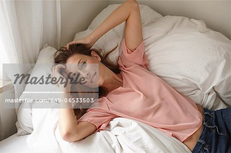 Smiling woman laying on bed Stock Photo - Premium Royalty-Free, Image code: 649-06533503