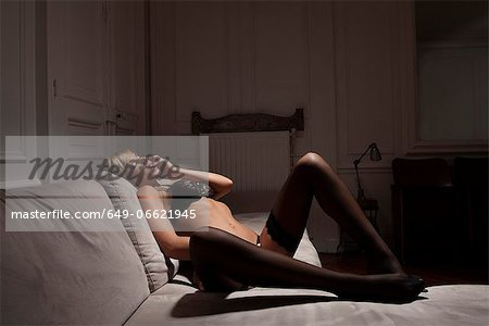 Woman in lingerie laying on sofa Stock Photo - Premium Royalty-Free, Image code: 649-06621945