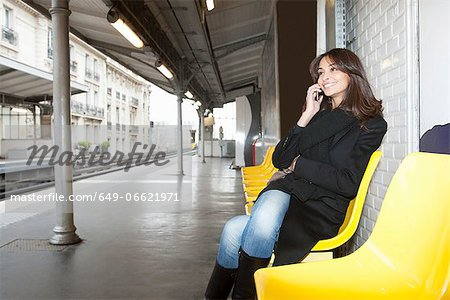 Woman on cell phone at train station Stock Photo - Premium Royalty-Free, Image code: 649-06621971