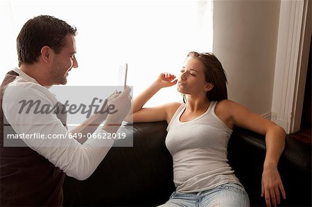 Man taking picture of girlfriend on sofa Stock Photo - Premium Royalty-Free, Image code: 649-06622019