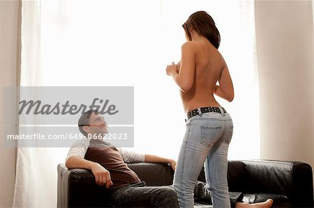 Woman stripping for boyfriend on sofa Stock Photo - Premium Royalty-Free, Image code: 649-06622023