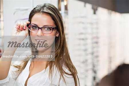 Woman trying on glasses in store Stock Photo - Premium Royalty-Free, Image code: 649-06622203