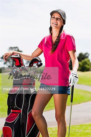 Woman holding golf bag on course Stock Photo - Premium Royalty-Free, Image code: 649-06622229