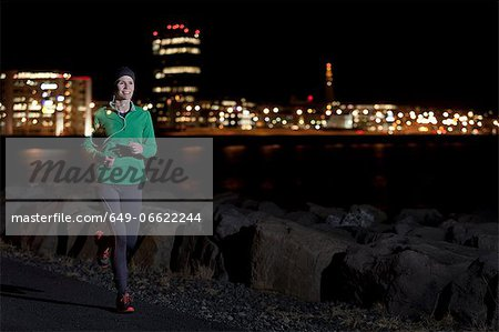 Woman running on waterfront at night Stock Photo - Premium Royalty-Free, Image code: 649-06622244