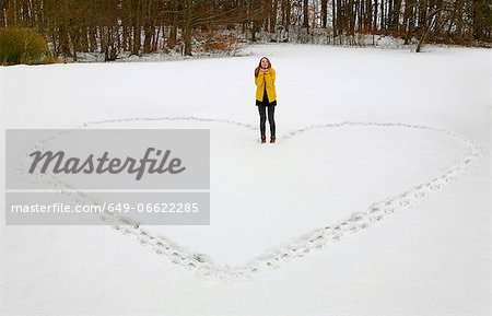 Woman making heart shape in snow Stock Photo - Premium Royalty-Free, Image code: 649-06622285