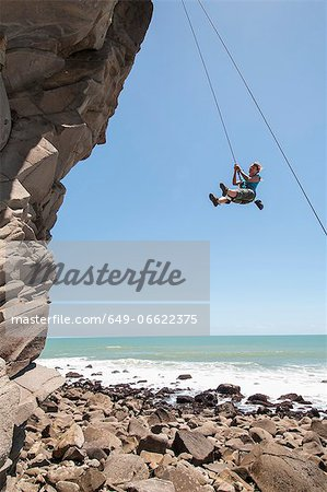 Rock climber abseiling jagged cliff Stock Photo - Premium Royalty-Free, Image code: 649-06622375
