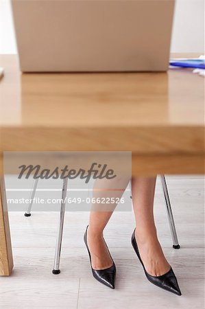 Businesswomans shoes under desk Stock Photo - Premium Royalty-Free, Image code: 649-06622526