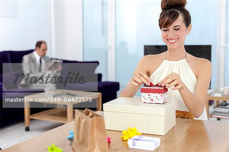 Woman opening presents at table Stock Photo - Premium Royalty-Free, Image code: 649-06622573