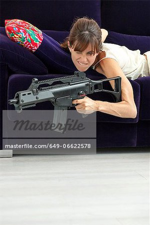 Woman shooting machine gun on sofa Stock Photo - Premium Royalty-Free, Image code: 649-06622578