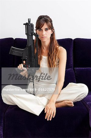 Woman holding machine gun on sofa Stock Photo - Premium Royalty-Free, Image code: 649-06622579