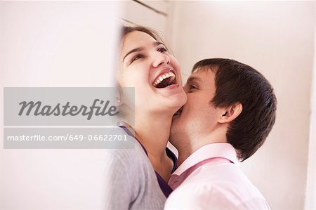 Man kissing girlfriend indoors Stock Photo - Premium Royalty-Free, Image code: 649-06622701