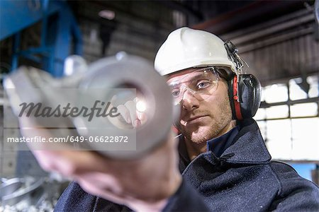 Worker inspecting metal in foundry Stock Photo - Premium Royalty-Free, Image code: 649-06622872