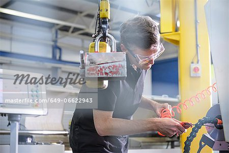 Worker using machinery in factory Stock Photo - Premium Royalty-Free, Image code: 649-06622943