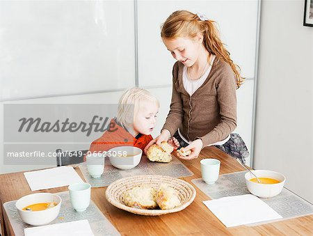 Girl serving brother lunch at table Stock Photo - Premium Royalty-Free, Image code: 649-06623058