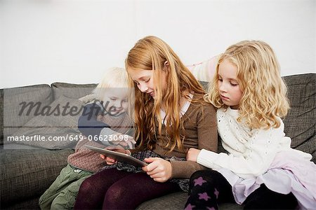Children using tablet computer on sofa Stock Photo - Premium Royalty-Free, Image code: 649-06623098
