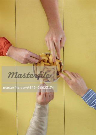 Overhead view of people sharing fries Stock Photo - Premium Royalty-Free, Image code: 649-06623174
