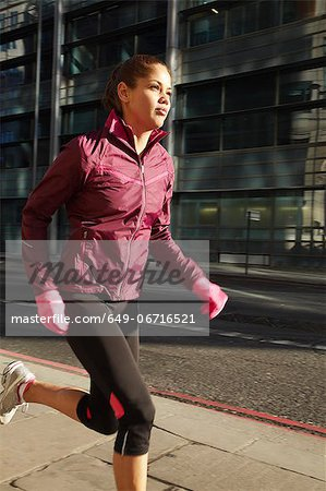 Woman running on city street Stock Photo - Premium Royalty-Free, Image code: 649-06716521