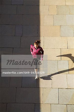 Woman running on city street Stock Photo - Premium Royalty-Free, Image code: 649-06716529
