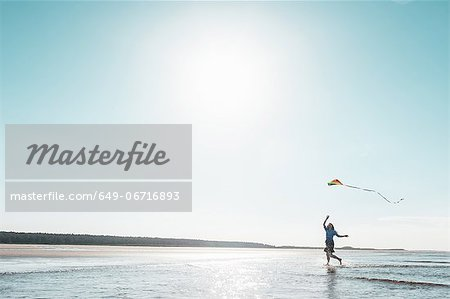 Woman flying kite on beach Stock Photo - Premium Royalty-Free, Image code: 649-06716893