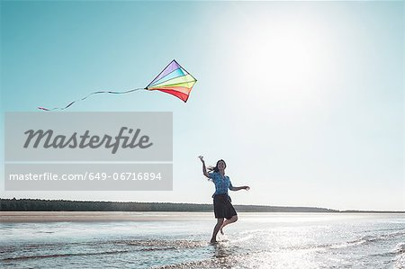 Woman flying kite on beach Stock Photo - Premium Royalty-Free, Image code: 649-06716894