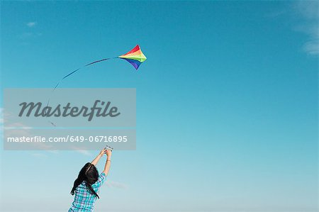 Woman flying kite outdoors Stock Photo - Premium Royalty-Free, Image code: 649-06716895