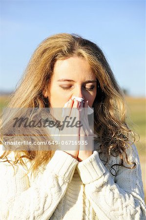 Woman blowing her nose outdoors Stock Photo - Premium Royalty-Free, Image code: 649-06716935